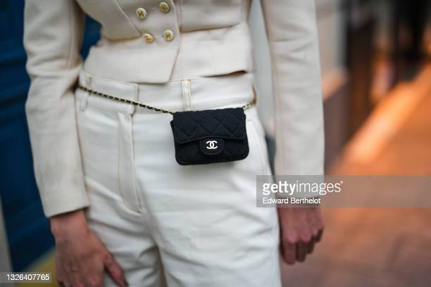 """Natalia Verza @mascarada.paris wears a beige Chanel double breasted jacket, a black Chanel mini belt bag, white flared pants, during the """"Chanel 5..."""