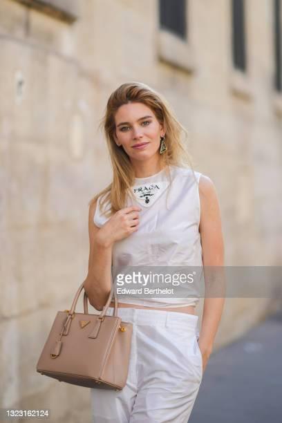 Natalia Verza @mascarada.paris wears a black and silver Prada earring, a white Prada logo tank-crop-top, white large pants, a beige shiny leather...