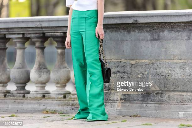 """Natalia Verza @mascarada.paris wears green flared pants """"color of the season"""" by Mihano Momosa , a black leather quilted Chanel bag, during a street..."""