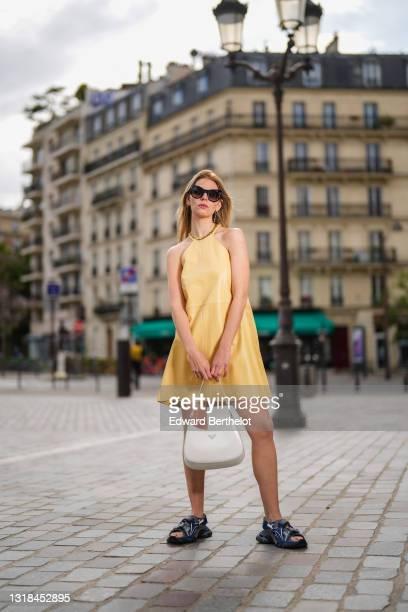 Natalia Verza @mascarada.paris wears Prada earrings, sunglasses, a mini mid-thigh pale pastel yellow gathered leather sleeveless dress from Aeron, a...