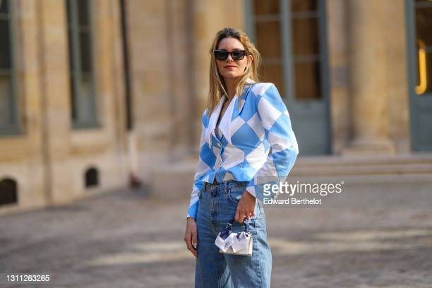 Natalia Verza @mascarada.paris wears sunglasses, a blue and white checked / argyle pattern printed blazer jacket with shoulder pads from Rowen Rose,...