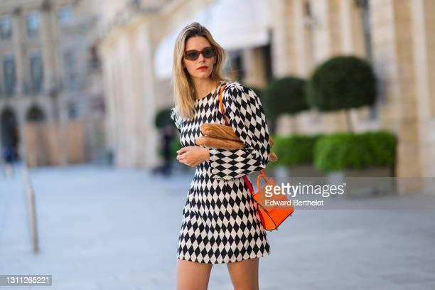 Natalia Verza @mascarada.paris wears sunglasses, a Rowen Rose check print mini dress with shoulder pads, a neon orange bag from Louboutin, carries...
