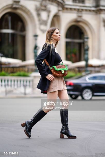 Natalia Verza wears a brown and green woven leather Fendi bag, a black oversized blazer jacket with shoulder pads from Barbara Bui, a black low neck...