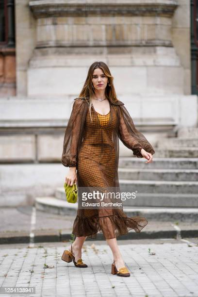 Natalia Verza wears a brown ruffled mesh checkered puff sleeves Fendi dress, over an orange checkered dress, a green corduroy gathered Fendi bag,...