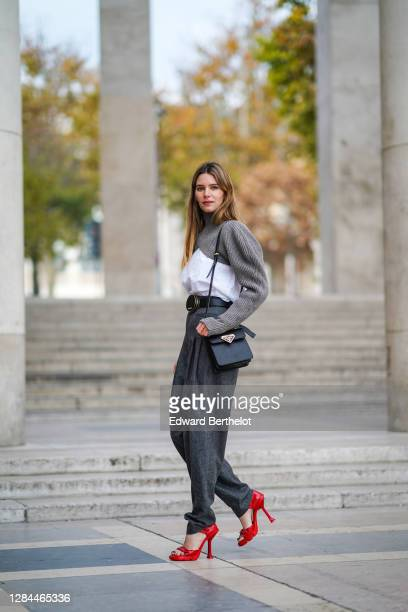 Natalia Verza wears a gray wool turtleneck pullover with a white shirt part and long sleeves from Nehera, gray large wool pants from Nehera, a Prada...