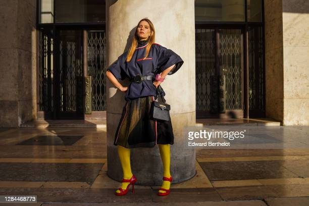 Natalia Verza wears a total look Prada made of a blue turtleneck top with short large sleeves and printed red stripes, a black leather belt circular...