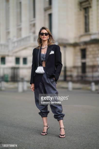 Natalia Verza wears a total Miu Miu look made of sunglasses, earrings, a chain metallic necklace, a black oversized blazer jacket, gray bras, a Miu...