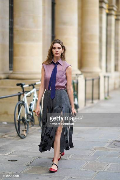 Natalia Verza wears a total Prada look: a purple sleeveless shirt, a blue tie, a gray fringed-edge wool midi skirt with embroidery, red leather shiny...