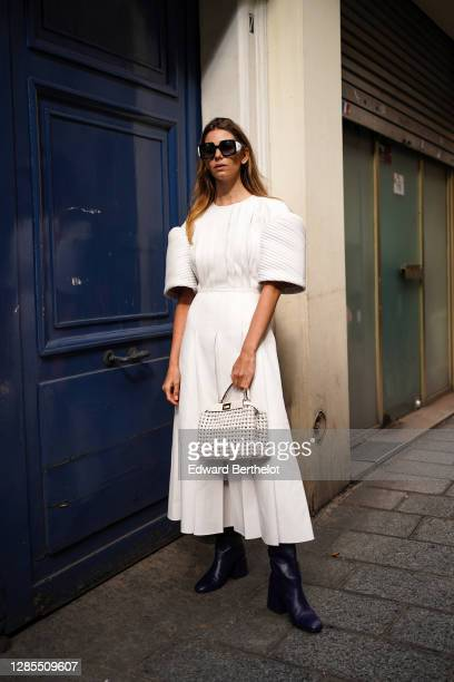 Natalia Verza wears a white pleated dress with puff shoulders, sunglasses, a white mesh woven leather bag, blue leather pointy boots, outside Paco...