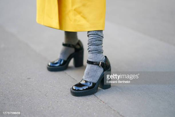 Natalia Verza wears a yellow long coat from Prada, Prada shoes, on September 10, 2020 in Paris, France.