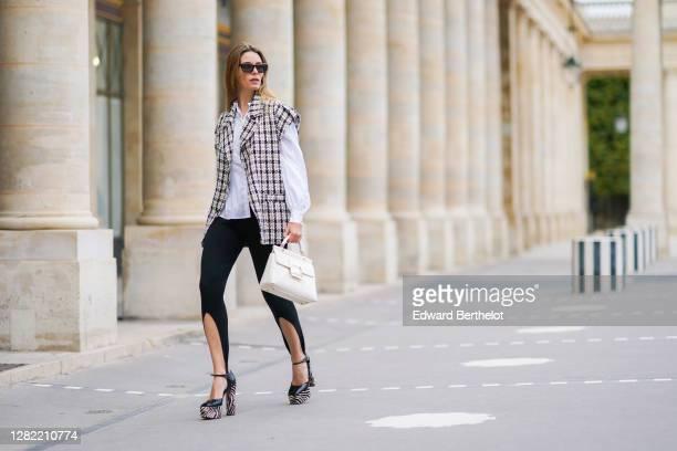 Natalia Verza wears black stirrup pants, sunglasses, Giuseppe Zanotti zebra print black and white platform shoes, an oversized sleeveless wool...