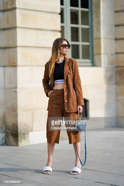 Natalia Verza wears Celine sunglasses, a necklace, a black Paco Rabanne cropped top, a Gestuz brown suede jacket, brown suede long shorts, white...