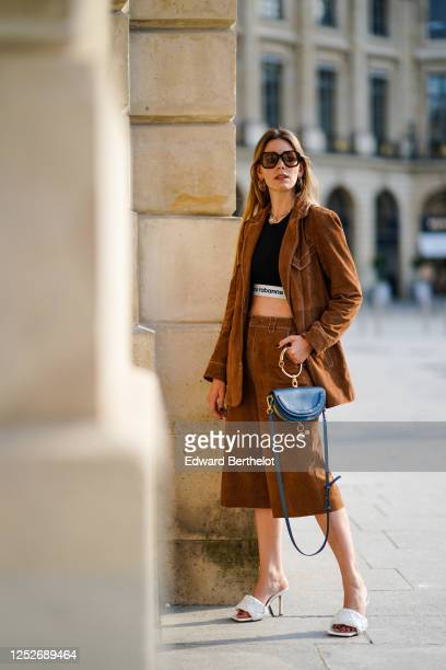 Natalia Verza wears Celine sunglasses a necklace a black Paco Rabanne cropped top a Gestuz brown suede jacket brown suede long shorts white Bottega...