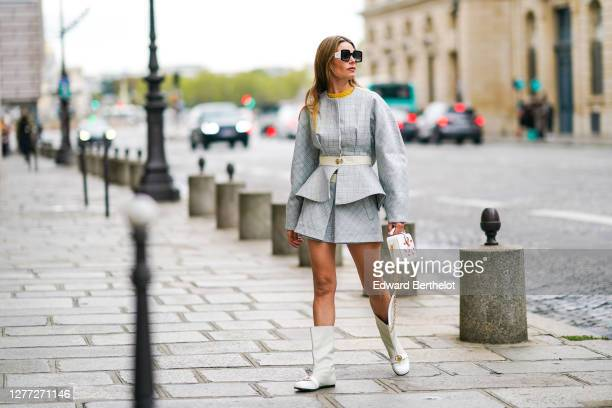 Natalia Verza wears Pucci sunglasses, a pale blue dress with geometric patterns from Lanvin, a Lanvin belt, a Lanvin bag with golden chain and...