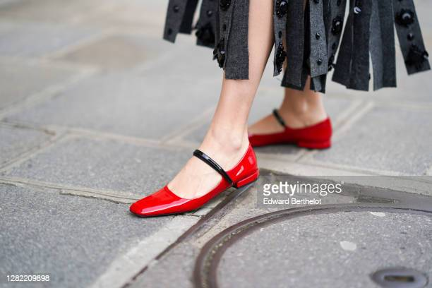 Natalia Verza wears red leather shiny Prada flat shoes, on October 12, 2020 in Paris, France.