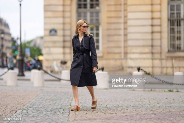 Natalia Verza wears sunglasses, a black short trench coat worn as a dress from Rosetta Getty, a Chanel micro bag, brown leather studded clogs from...