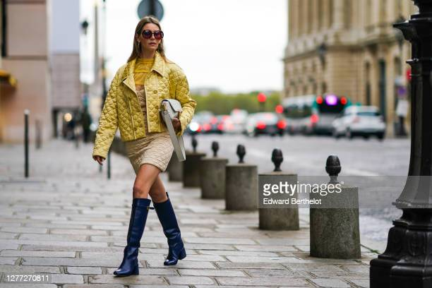 Natalia Verza wears sunglasses, a Fendi full outfit made of a yellow padded silky jacket, a Fendi leather monogram bag, a beige padded dress with...