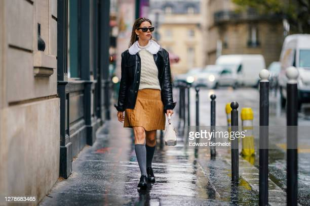 Natalia Verza wears sunglasses, a white wool woven pullover, a white ruffled collar, a brown/orange pleated skirt, a black leather jacket, gray high...