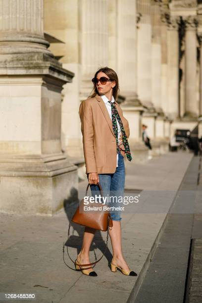 Natalia Verza wears sunglasses from Celine, a Paul & Joe beige blazer jacket, a white shirt, a colored floral print tie from Paul & Joe, blue denim...