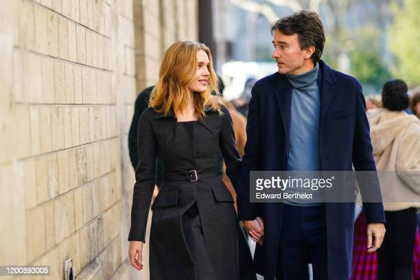 Natalia Vodianova wears a black dress and a belt Antoine Arnault wears a blue turtleneck pullover and a blue long coat outside Dior during Paris...