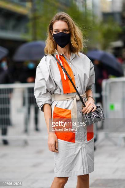 Natalia Vodianova wears a black protective face mask, a gray and orange trench coat / dress, a Vuitton bag, black leather pointy shoes with golden...