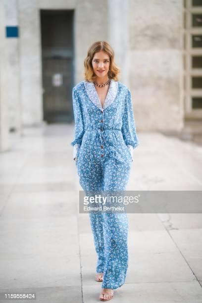 Natalia Vodianova wears a blue floral print jacket, a necklace, flare pants, outside the Ulyana Sergeenko show, during Paris Fashion Week -Haute...