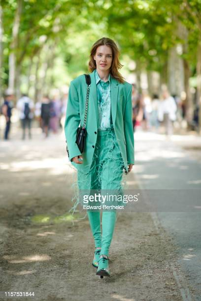 Natalia Vodianova wears a green blazer jacket, a green shirt, a skirt with fringes, green pants, shoes, a bag, outside Berluti, during Paris Fashion...