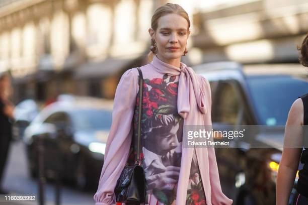 Natalia Vodianova wears a Valentino bag a pink top with printed flowers roses and an orange striped lower part outside Valentino during Paris Fashion...