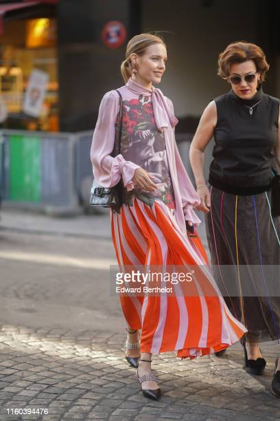 Natalia Vodianova wears a Valentino bag a pink top with printed flowers roses and an orange striped lower part outside Valentino black shoes during...