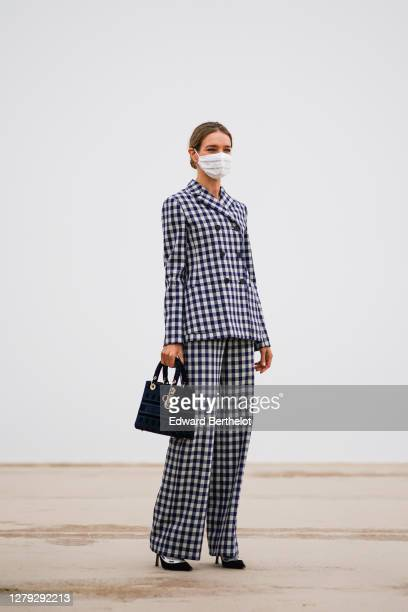 Natalia Vodianova wears a white protective face mask, a black and white checked blazer jacket, a Dior Lady Dior bag, flared pants, J'Adior pointy...
