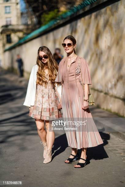 Natalia Vodianova wears sunglasses a powder pink pleated dress black sandals with mirror heels a sagegreen handbag her half sister Kristina Kusakina...