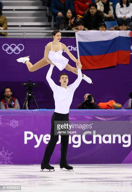 Natalia Zabiiako and Alexander Enbert of Olympic Athlete from Russia compete as a fan holds the Russian flag during the Pair Skating Free Skating at...