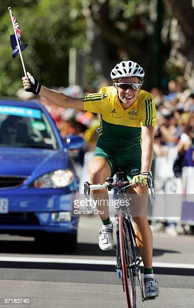 Natalie Bates of Australia waves an Australian flag as she crosses the line to win the Women's Road Race at the Royal Botanic Gardens Circuit during...
