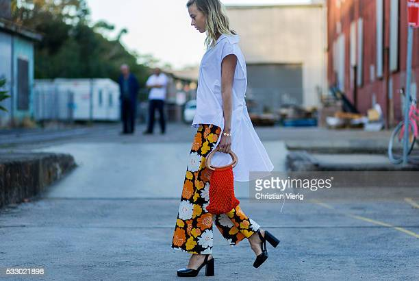 Natalie Cantell wearing a white sleeveless blouse pants with floral print heels and a fishnet bag at MercedesBenz Fashion Week Resort 17 Collections...