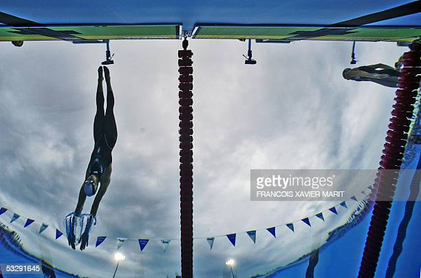 Natalie Coughlin of the US dives into the pool to position herself for the start of the women's 100m backstroke final 26 July 2005 at the XI FINA...