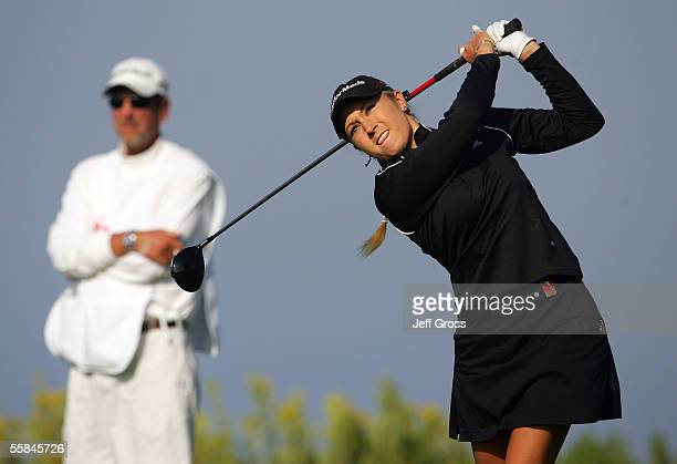 Natalie Gulbis hits a tee shot on the thirteenth hole as her caddie Greg Sheridan looks on during the final round of the Office Depot Championship at...