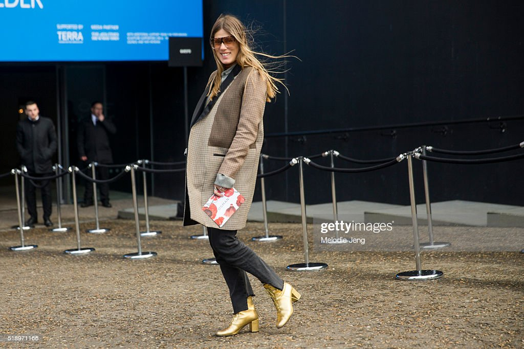 Natalie Hartley, Glamour Magazine Fashion Director, wears a brown and yellow tartan Celine coat, customized black jeans, and gold lace-up Saint Laurent booties during London Fashion Week Autumn/Winter 2016/17 at Christopher Kane show at Tate Modern on February 22, 2016 in London, England.