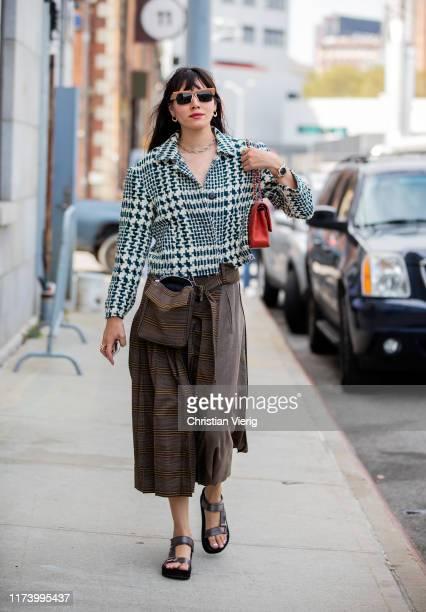 Natalie Lim Suarez is seen wearing brown checkered two tone skirt blazer outside Michael Kors during New York Fashion Week September 2019 on...