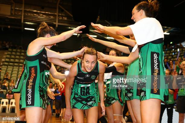 Natalie Medhurst of the Fever walks thru a guard of honour by team mates after playing her 200th game during the round 10 Super Netball match between...