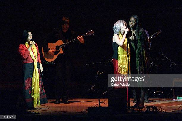 Natalie Merchant Emmylou Harris and Dana Bryant on stage performing during the Tibet House Benefit Concert 2001 with artistic director Philip Glass...