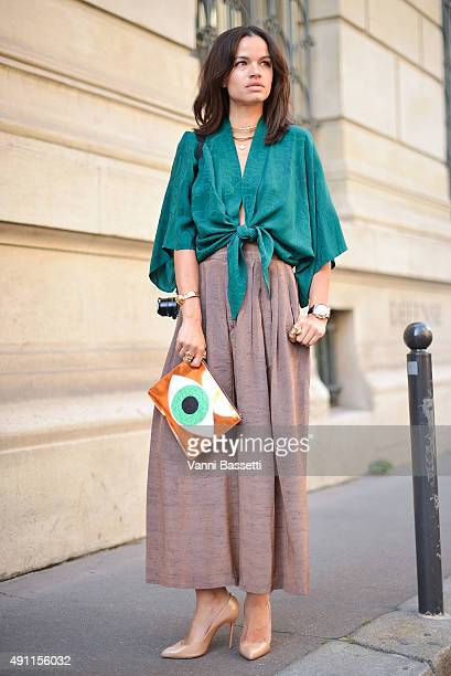 Natalie Nieves poses wearing vintage top and skirt, Jennifer Fisher jewelry and Poppy Lissiman clutch after the Vivienne Westwood show at the...