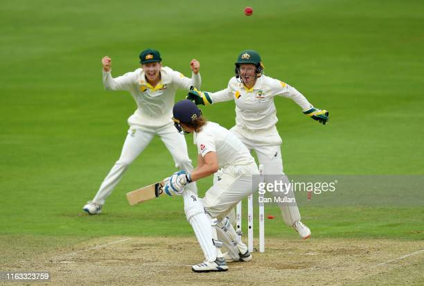 Natalie Sciver of England is bowled by Jess Jonassen of Australia as Meg Lanning and Alyssa Healy of Australia celebrate during day four of the Kia...