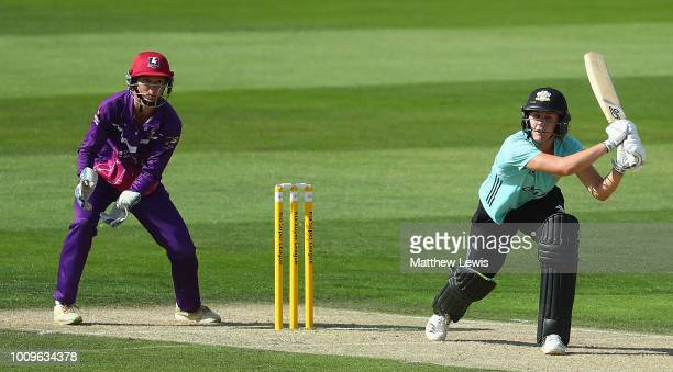 Natalie Sciver of Surrey Stars hits the ball towards the boundary as Amy Jones of Loughborough Lightning looks on during the Kia Super League match...