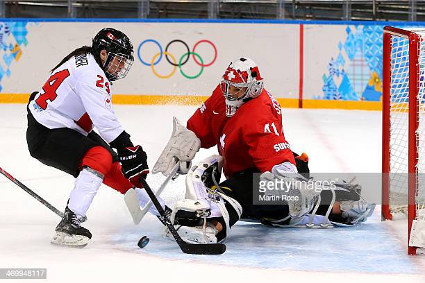 Natalie Spooner of Canada fights for the puck against Florence Schelling of Switzerland during the Women's Ice Hockey Playoffs Semifinal game on day...