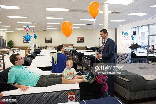 Natalie Tolley listens to Mattress Warehouse salesman Mike Eleyn as her husband keeps and eye on daughters 15 monthold Claire and 4 yearold Sophie in...