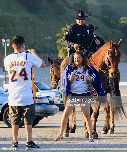 Natalie Velazquez and Fernando Mejia have their photo taken with an LAPD officer in the parking lot at Dodger Stadium on April 14 2011 Security is...