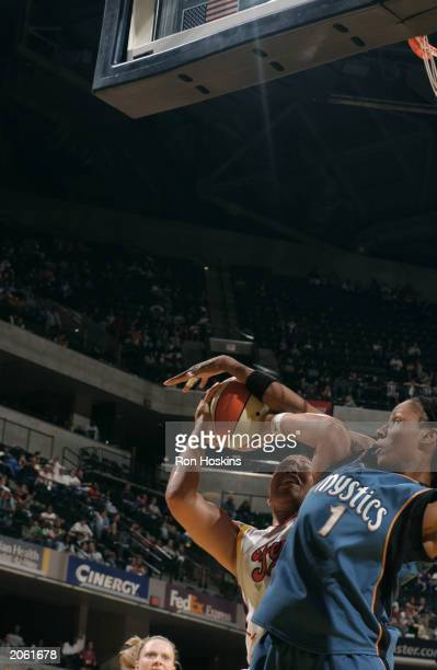 Natalie Williams of the Indiana Fever gets blocked by Chamique Holdsclaw of the Washington Mystics during the WNBA game at Conseco Fieldhouse on May...