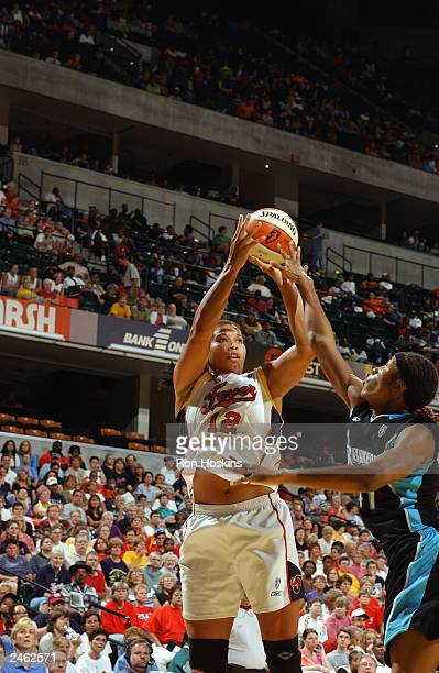 Natalie Williams of the Indiana Fever shoots over Pollyanna Johns Kimbrough of the Cleveland Rockers during the game at Conseco Fieldhouse on August...
