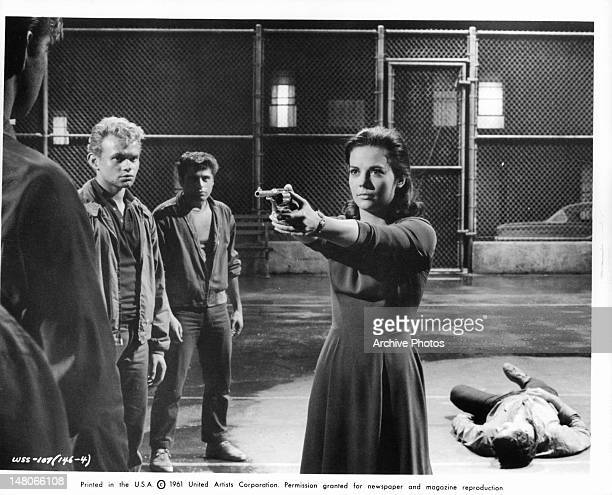 Natalie Wood pointing a gun at a man as two men watch from the side line in a scene from the film 'West Side Story' 1961