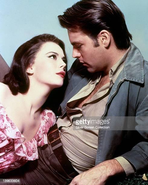 Natalie Wood , US actress, gazing at her husband, Robert Wagner, US actor, in a studio portrait, against a light blue background, circa 1975.